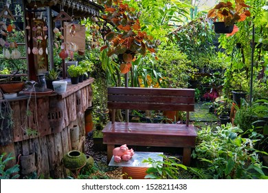Chair in the garden. Garden chairs and mini-bars. Backyard with a counter bar and long seating in a shady tree garden. Thailand style.