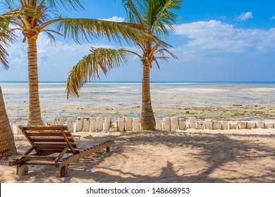 Chair and green trees on a white sand beach. Watamu, Kenya - Africa