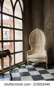 A chair near window on checker floor