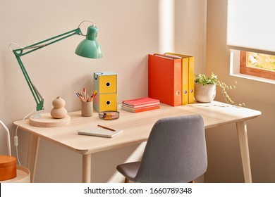 Chair placed near table with lamp and colorful stationery in cozy home office in morning