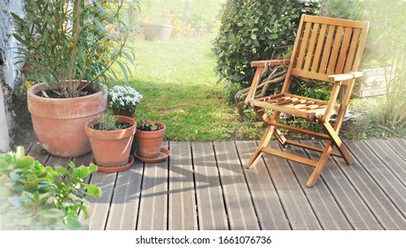 chair and potted plant on wooden terrace in summer
