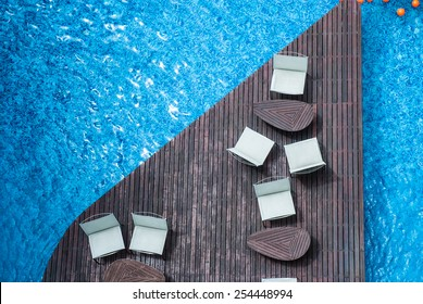 chair relax on in holiday swimming pool with clear blue water /  Empty sunbeds by the resort pool