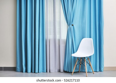 Chair and room window with white and blue curtains