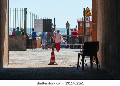 a chair and a skittle placed in the presence of an open gate, while a lady is coming out