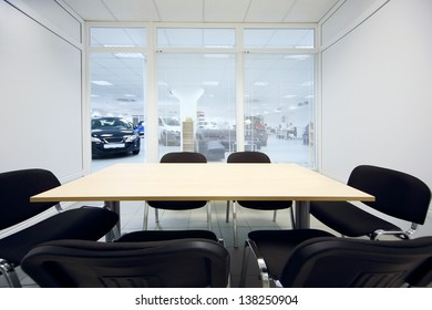Chair and table in small room and new cars in office of car shop through window visible.