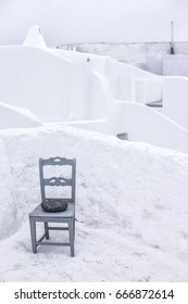 Chair and traditional white washed roofs. Architecture of Pyrgus Santorini island Greece