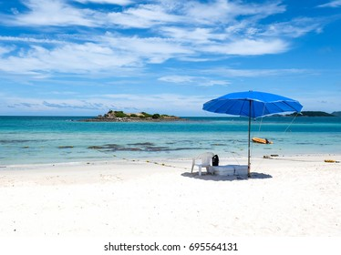 chair, umbrella and yellow boat at sea with blue sky and white cloud in sunshine day