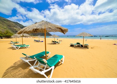Chair and umbrellas on Teresitas beach in summertime, Tenerife holiday and relaxation,