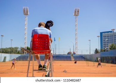 Chair umpire (tennis referee) on the position during game. the umpire is hot. Playing tennis on the ground orange court. Hot refereeing