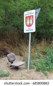 Chair under locality marking and traffic sign, Podkerepušky, Bratislava, Slovakia