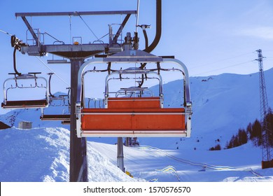 Chairlift or elevated passenger ropeway at ski area. Winter leisure and sports. Mountain snowboard resort.