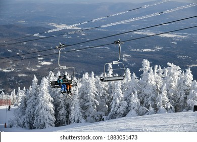 Chairlift with people at Stowe Ski Resort in Vermont, view to the Mansfield mountain slopes, December fresh snow on trees early season in VT,  hi-resolution image