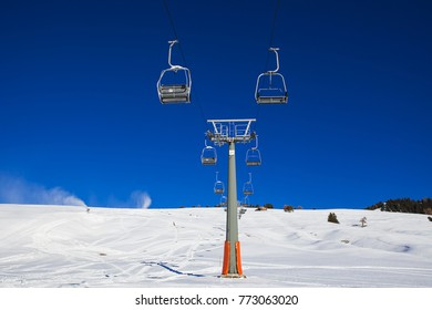 Chairlift without people. The cable car on the blue sky in the Dolomites. Cableway in the mountains without people. Artificial snowing ski slope by Snow maker. Alpe di Siusi, Italy in winter.