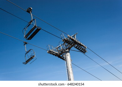 Chairlifts on a blue clear ski during on a bright day.