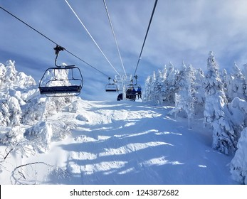 Chairlifts and trails at ski resort on a sunny, beautiful day.