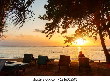 Chairs with beautiful sunrise at beach. Famous travel destination in Sanur, Bali, Indonesia. Relaxing, travel concept