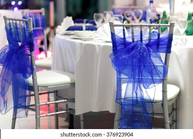 Chairs with blue fabric decor in the restaurant. Wedding hall decorations.