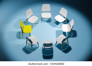 Chairs in a circle in an empty dark studio room. One chair stands out. The concept of leadership and individuality
