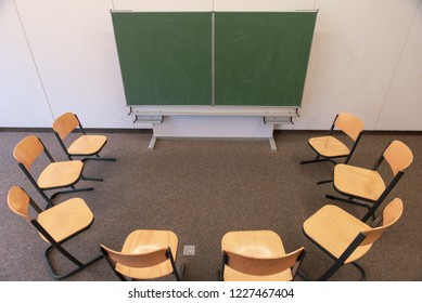 Chairs in a circle in front of a chalkboard in classroom