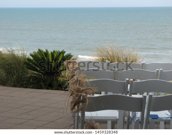 Chairs facing the ocean for a wedding.