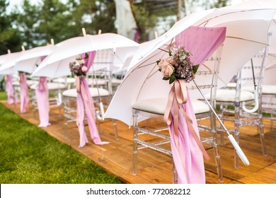 Chairs, flowers and umbrellas at an outdoor ceremony.