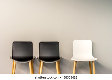 Chairs in modern design arranged in front of the gradient grey wall for interior or graphic backgrounds. The picture can be used as a metaphor for job hiring to represent the hiring position.
