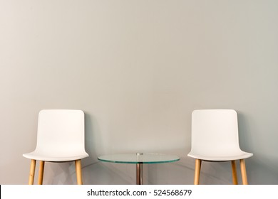 Chairs in modern design arranged in front of the gradient grey wall for interior or graphic backgrounds. The chairs can be used to represent interview sessions or waiting rooms for ads purpose.
