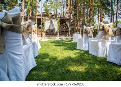 Chairs for the off-site wedding ceremony are decorated with canvas bows leading to a rustic arch.