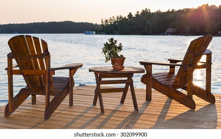Chairs on a deck overlooking a lake at sunset.