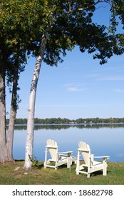 Chairs on the shoreline of a serene lake in Minnesota