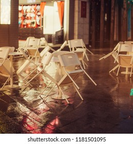 Chairs on the street. It is raining