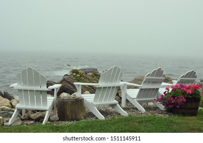 Chairs overlooking the water in Maine on a very foggy day