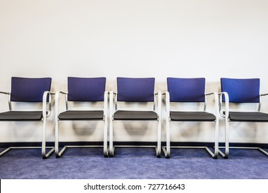 Chairs row on the blue carpet floor at the wall. Waiting room in office, hospital, clinic, education or other institution. Place for waiting in line of job interview and casting. Interior concept.