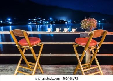 Chairs sipping tea riverside at night time, Lee wine rak thai, Maehongson, Thailand