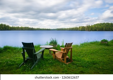 Chairs sit on the grass facing a lake waterfront landscape paradise in Ontario, Canada. The long exposure shot is offering a silky water effect. A cottage nestled between trees is visible.