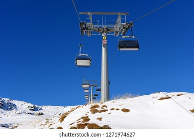 Chairs of ski-lift in the ski resort in the early morning. Winter snowboard and skiing concept. Italia, Europe.