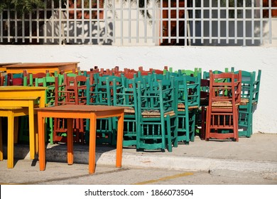 Chairs stack, closed restaurant Covid-19 Pandemic lockdown. Wooden tavern seats stacked outdoor. Crete Island, Greece