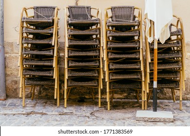 Chairs stacked of a street caf?, terrace caf?, in front of a restaurant. It is closed due to coronavirus in a square of european city, outdoor.
