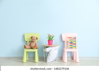 Chairs and table near color wall in children's room