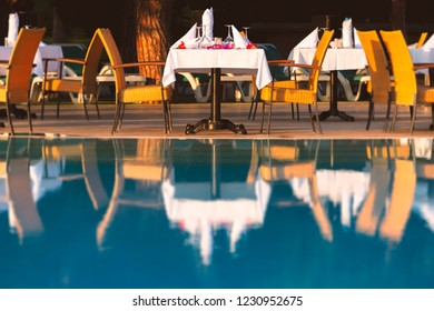 Chairs and table near pool at hotel restaurant. Cutlery and napkings on tables. Resort life on holidays.