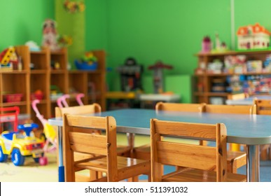 Стулья, стол и игрушки. Интерьер детского сада.