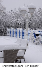Chairs, tables and bike covered with snow in the outdoor restaurant