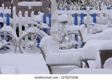 Chairs, tables and bikes covered with snow in the garden