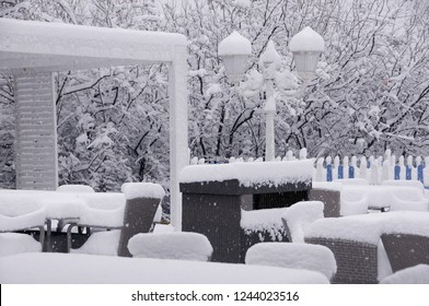 Chairs and tables covered with snow in the outdoor restaurant