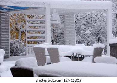 Chairs and tables covered with snow in the outdoor restaurant in the late fall