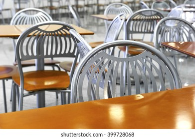 Chairs and tables in fast food restaurant, cafe silver steel furniture with orange wooden seats and working surfaces, food court, nutrition industry, selective focus