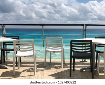 Chairs and tables on a terrace with the Caribbean Sea in background
