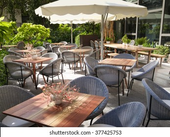Chairs and tables of a restaurant seating outside with parasols.