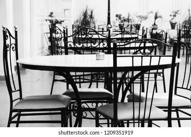 Chairs and tables in a restaurant setting. Black and white.