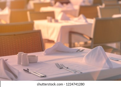 Chairs and tables at sunset at hotel restaurant. Cutlery and napkings on tables.